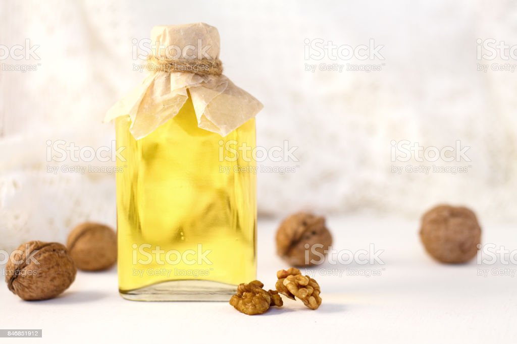 Walnut oil in bottle on white wooden background. Selective focus. stock photo
