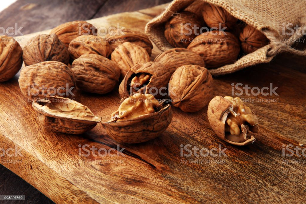Walnut. Walnut kernels and whole walnuts in burlap sack stock photo