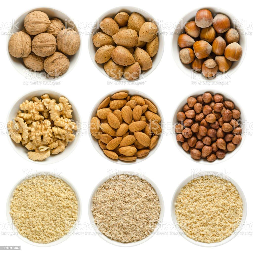 Walnuts, almond, hazelnuts in white bowls on white background stock photo