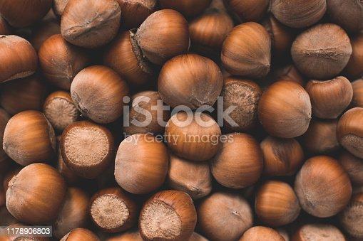 Pile of unpeeled hazelnuts closeup. Autumn season harvesting. Top view.
