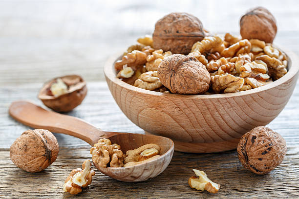 Walnuts in a bowl. Walnuts in a bowl on old table closeup. walnut stock pictures, royalty-free photos & images