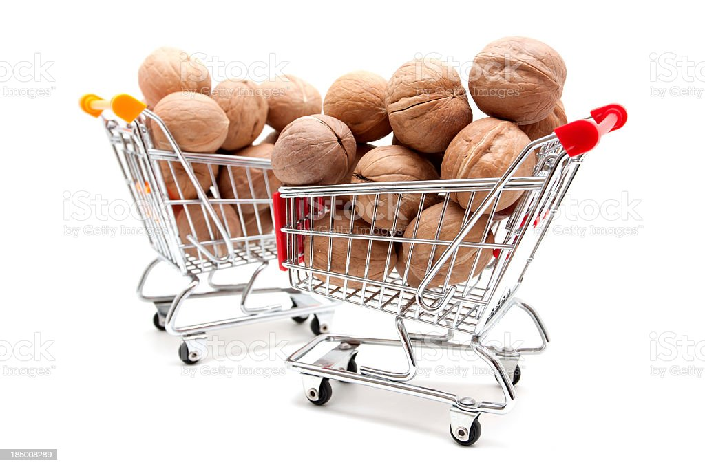 Walnuts in shopping cart isolated on white background royalty-free stock photo