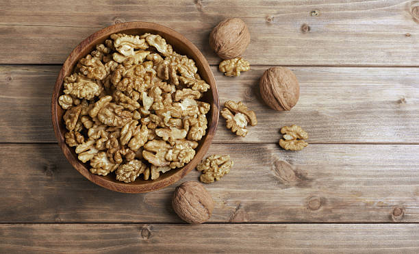 walnuts in wooden bowl - walnut stock photos and pictures
