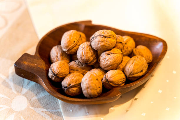 Walnuts lie in a bowl on grandmother's table stock photo