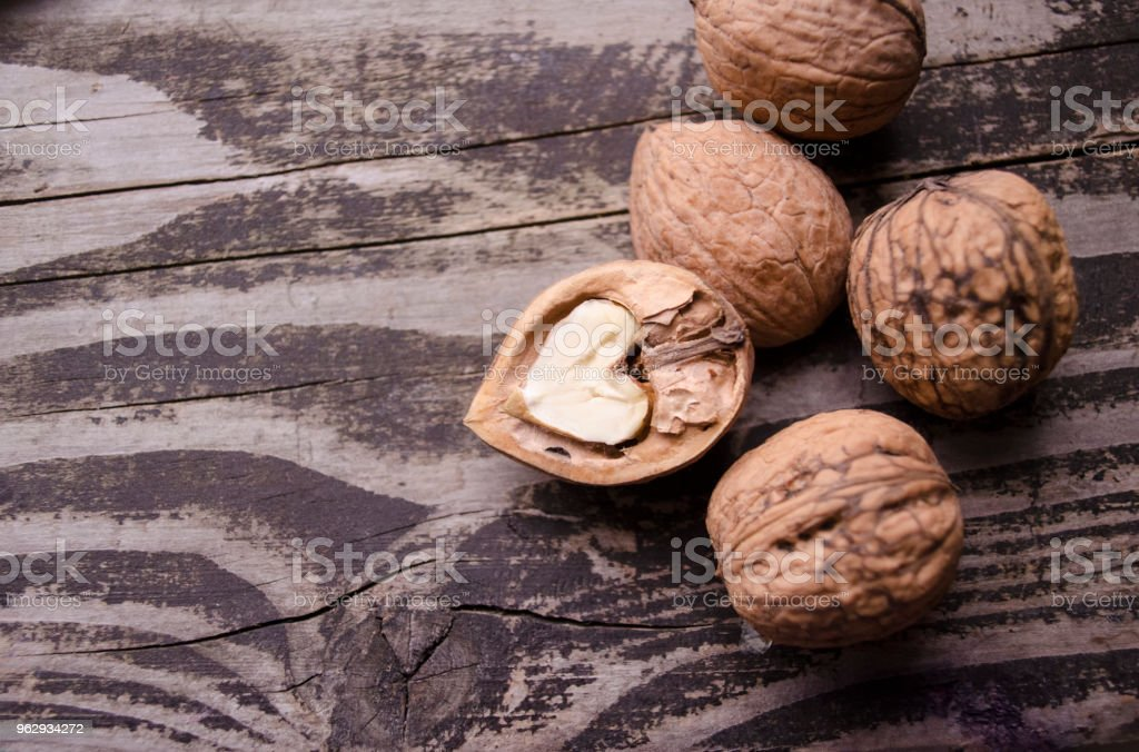 Walnuts on a grey textured wooden table. Assortment of nuts isolated on rustic old wooden background and splintered walnut with heart-shaped core. Walnuts close up royalty-free stock photo