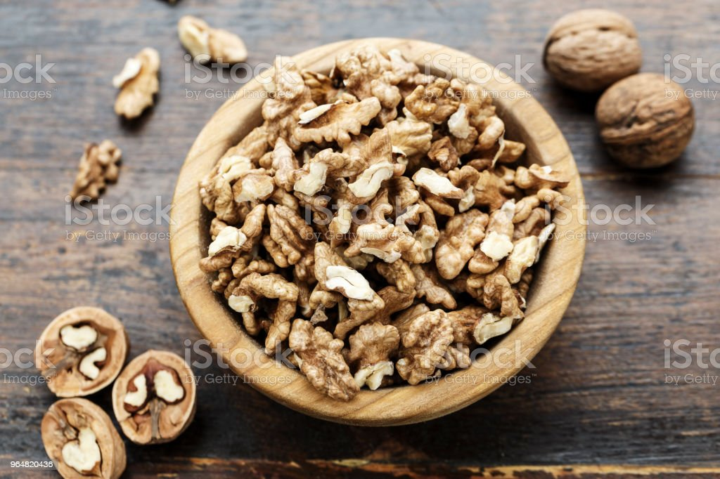walnuts on a wooden background, in a plate. royalty-free stock photo