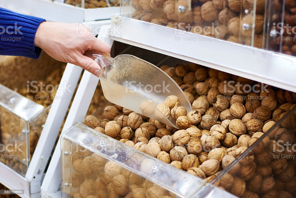 Walnuts on store shelves and hand buyer with shovel stock photo
