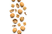 top view of walnuts closed and broken scattered on a white background with copy space