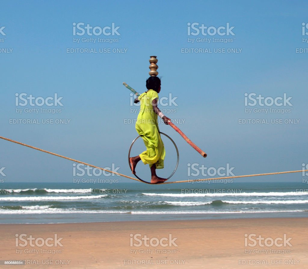 Wandering indian tightrope walker playing on the beach of Goa stock photo