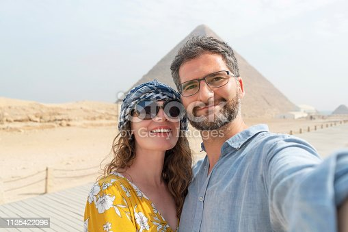 Caucasian couple taking selfie while visiting Pyramids of Giza in Egypt.