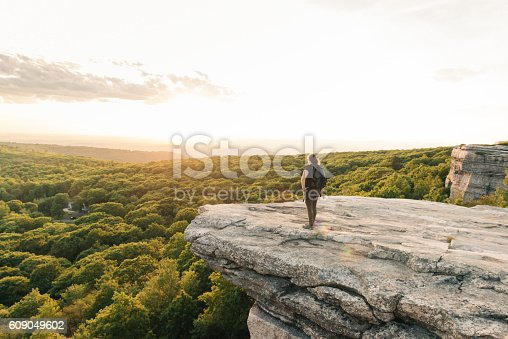This is a horizontal, color photograph of woman hiking stopping to enjoy the view from Sam's Point Preserve in the Shawangunk Mountains. These mountains are part of the Appalachian Mountains. Green trees fill the valley below the cliffs of the mountain ridge in upstate New York, Ulster County. Photographed with a Nikon D800 DSLR camera.
