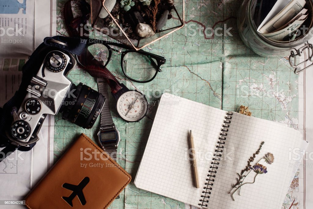 wanderlust and adventure concept, jar with money for travel compass camera passport on map, top view, notebook with flowers, vintage toned image - Foto stock royalty-free di Analogico