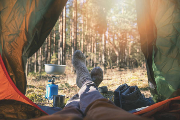 wanderlust outdoor camping - traveler feet out of the tent stock photo