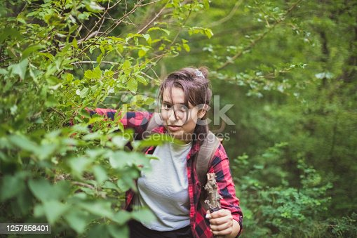 Closeup view of a woman fully equipped for a day in nature. She is walking in the forest with a big stick in her hand and looking at the camera.