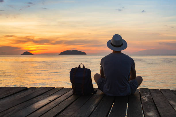 wanderlust travel, tourist with backpack sitting near the sea stock photo
