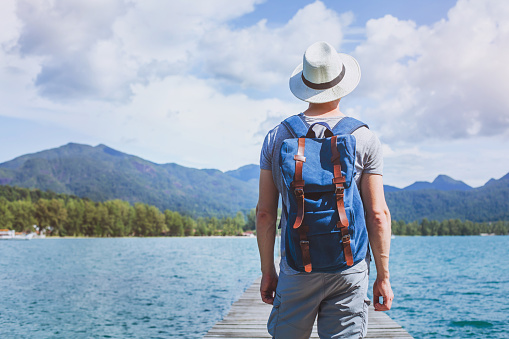 istock Wanderlust travel, young tourist traveler with backpack on summer beach. 1062128914