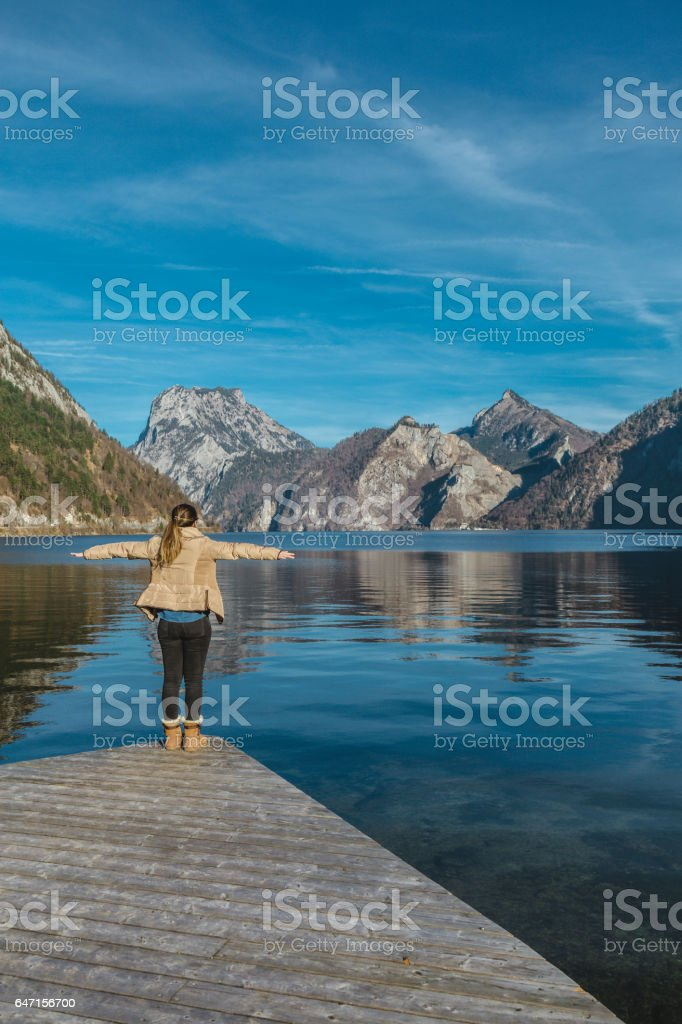 Wanderlust with arms outstretched on a lake stock photo