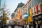 Beijing, China-November 23, 2019: People walk on Wangfujing Street, the most famous shopping street in Beijing, with nearly 300 shops and shopping centers. This is a popular place for locals and tourists around the world. The tree-lined pedestrian area is home to shops, ranging from high-end designers to everyday consumer goods stores.