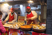Beijing, China - December 8, 2015:  Vendor are selling different unique food on this gourmet street. Tourist are enjoy the gourmet on this snack street. It is popular tourist point.