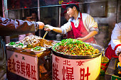 Beijing, China - October 24, 2014: Wangfujing Snack Street at night. Chinese chef selling Ancient Beijing Soiled Pork Tripe. Located in Beijing, China.