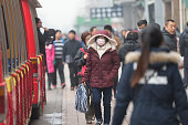 Beijing, China - December 8, 2015: People walking at Wangfujing Street under a heavy smog day . ŒSome people wearing mask with air filter to against air pollution. Wangfujing is a 700-year-old commercial street.