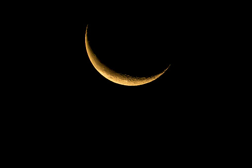 Waning crescent moon rising in the early dawn.