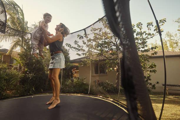 wanna go higher? - mãe criança brincar relva efeito de refração de luz imagens e fotografias de stock