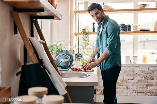 Handsome young man in casual wear chopping food and smiling while standing in the kitchen at home