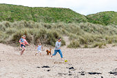 A side view of a same sex couple at the beach with their daughter and son, they are all running down the dunes chasing a soccer ball. One woman is holding their son in her arms. Their family dog is watching them.