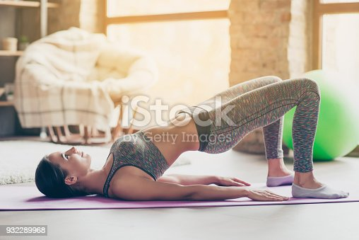 istock I want to be attractive and sportive! Cheerful graceful strong energetic enduring sexy muscular girl wearing tight fashionable outfit is doing exercises to build muscles at class 932289968