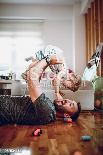 Father Having Fun With Baby Son In Living Room