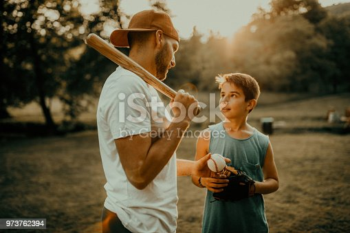 Father and son playing baseball in meadow