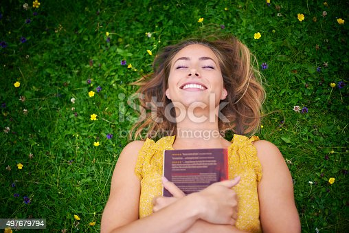 High angle shot of a carefree young woman relaxing on the grass with a bookhttp://195.154.178.81/DATA/i_collage/pi/shoots/805935.jpg