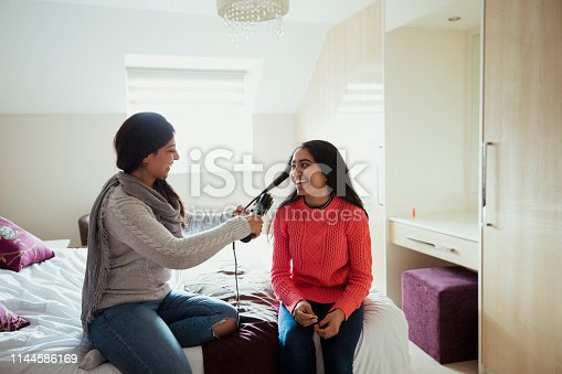 A mother and her daughter are sitting on her bed whilst she curls her daughter's hair. They both look happy to be bonding and sharing this moment together.