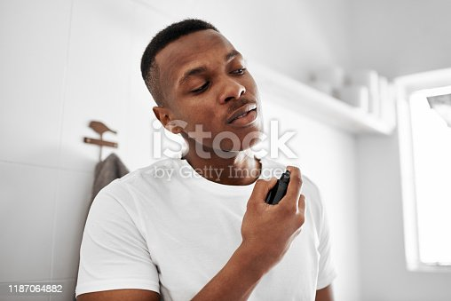 Shot of a young man spraying himself with deodorant