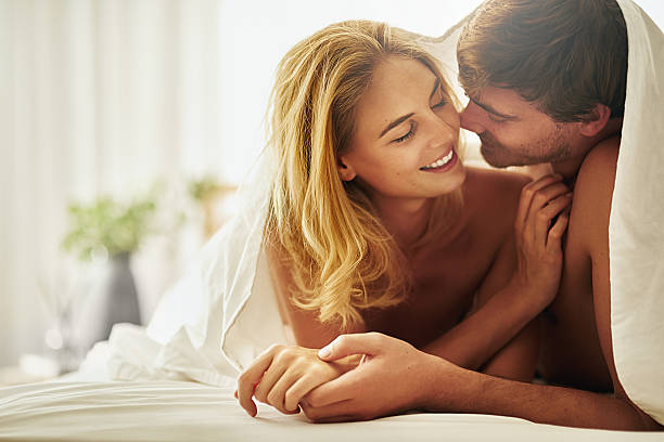 I want you and only you Shot of a young couple sharing an intimate moment under the covers in bed real couples making love stock pictures, royalty-free photos & images