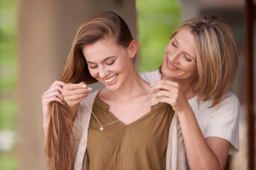 A mother lovingly putting a necklace around her daughter's neck