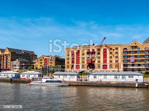 Wapping Pier beside the River Thames in East London on a sunny spring day. The pier is used by pleasure craft and commuter boats. Behind it is King Henry's Wharf, once a warehouse but now a development of houses and apartments. Nearby is the famous Captain Kidd pub. (Incidental people.)