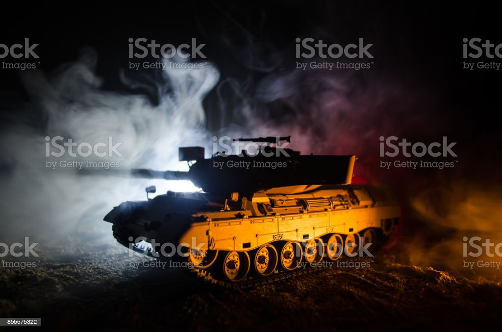 War Concept. Military silhouettes fighting scene on war fog sky background, German tank in action Below Cloudy Skyline At night. Attack scene. Armored vehicles stock photo