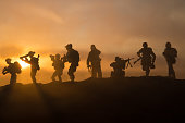 istock War Concept. Military silhouettes fighting scene on war fog sky background, World War Soldiers Silhouette Below Cloudy Skyline At sunset. 1254467561