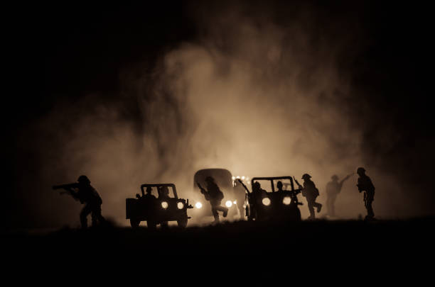 War Concept. Military silhouettes fighting scene on war fog sky background, World War Soldiers Silhouettes Below Cloudy Skyline At night. Attack scene. Army jeep vehicles with soldiers. stock photo