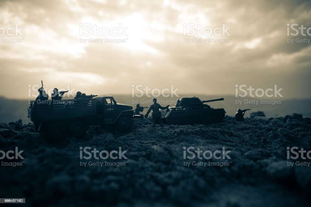 War Concept. Military silhouettes fighting scene on war fog sky background, World War Soldiers Silhouettes Below Cloudy Skyline At night. Attack scene. Armored vehicles. Tanks battle. stock photo