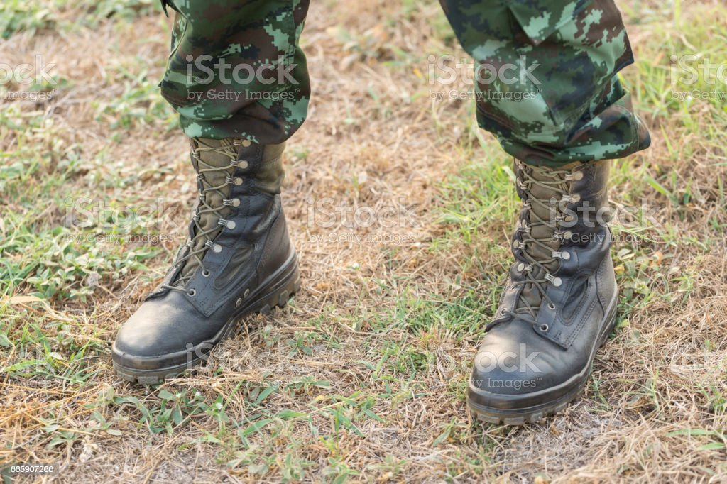 war, hiking, army and people concept - close up of soldier boots and hands tying bootlaces in forest foto stock royalty-free