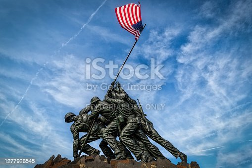 Arlington, Virginia / USA - September 7, 2018: The US flag waves over the US Marine Corps War Memorial designed by sculptor Felix de Weldon and architect Horace W. Peaslee which was unveiled on November 10, 1954.