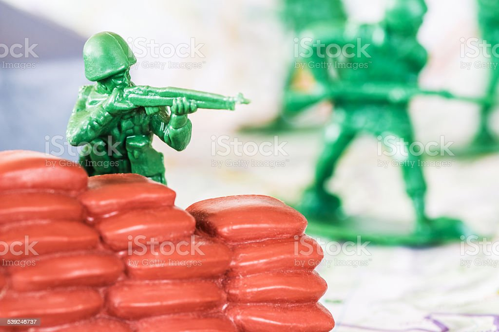 War with little green plastic soldier with rifle stock photo