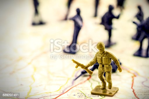 Concept of war, with little green soldier toy running with a weapon in his hands in selective focus with blurred blue soldier in background, placed on a military map. Macro shot.