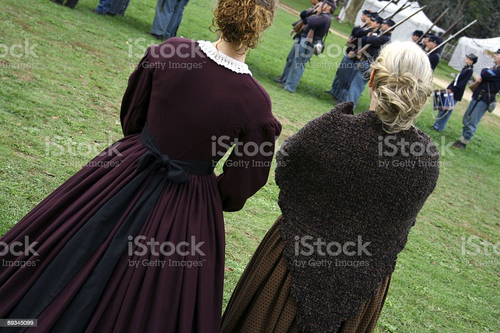War Women: Ladies in 1860 costume watch Union soldiers stock photo