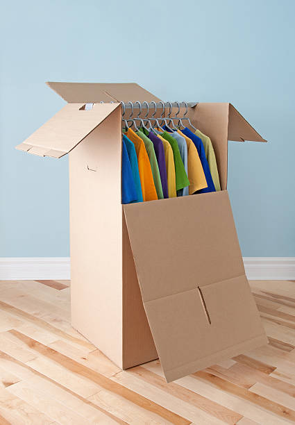 Wardrobe box with colorful clothing, ready for moving stock photo
