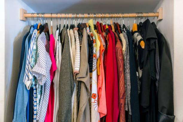 kleiderschrank voll von unterschiedlicher farbe, material und textur kleidung, accessoires im schrank - bügelsysteme stock-fotos und bilder