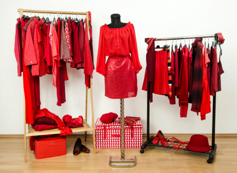Wardrobe with all shades of red clothes, shoes and accessories.